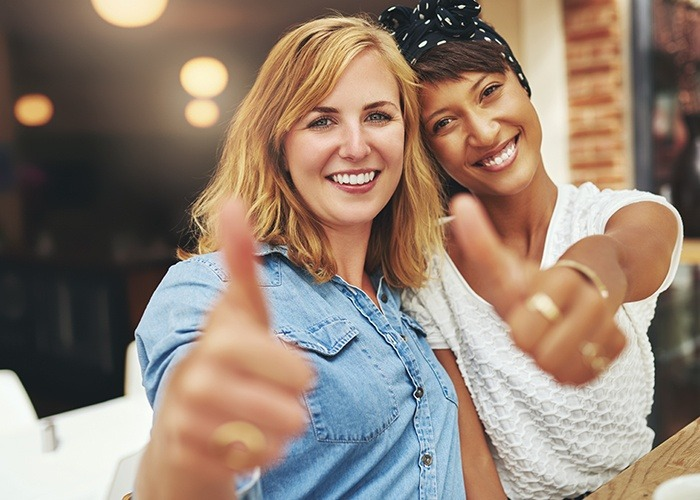 Two smiling women giving thumbs up after cosmetic dentistry
