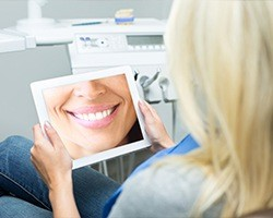 Woman looking at digital image of her smile