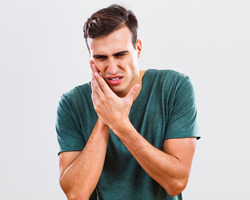 man in green shirt with toothache in need of emergency dentistry
