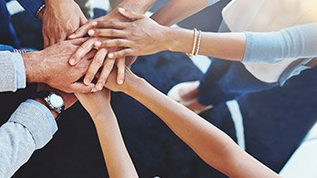 Group of people in circle touching hands