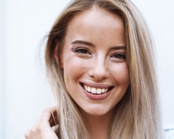Blond woman with attractive teeth smiling at camera