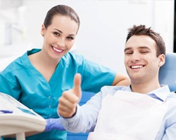 Smiling man in dental chair gives a thumbs up