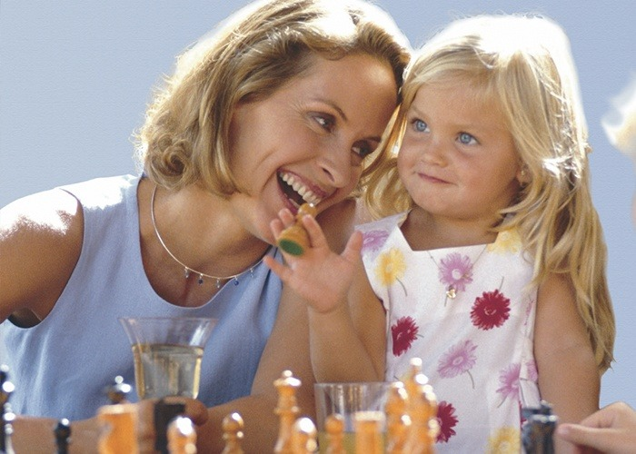 Smiling mother and daughter playing chess