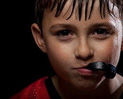 Young boy holding athletic mouthguard