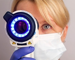 Woman holding oral cancer screening tool