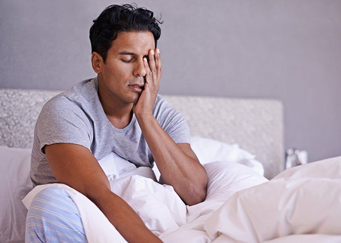 Tired man in need of sleep apnea therapy frustrated with head in hands