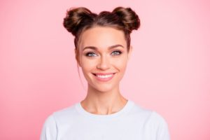 girl with space buns smiling with a pink background