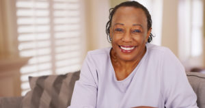 smiling woman with dentures should consider dental implants