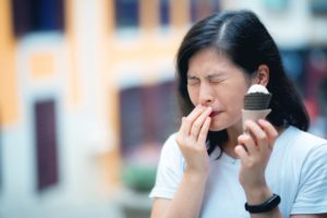 Woman with ice cream and toothache because of sensitive teeth