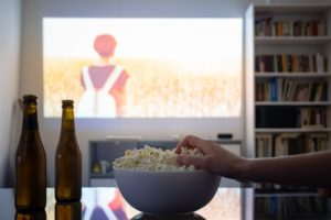 person snacking while binge-watching tv