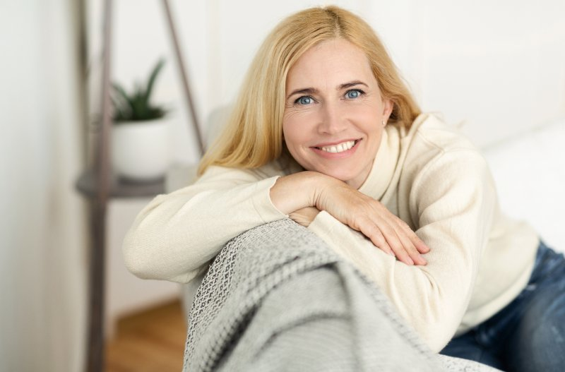 a middle-aged woman leaning on a couch and smiling after receiving her dental implants
